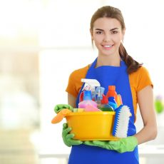 Woman in rubber gloves holding basin with detergents on blurred background